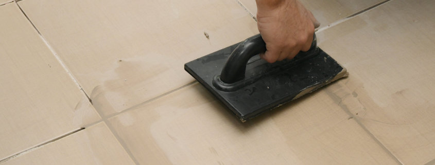 applying grout for natural stone tiles with a trowel